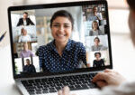 Woman sit at desk looking at computer screen where collage of diverse people webcam view. Indian ethnicity young woman lead video call distant chat, group of different mates using videoconference app